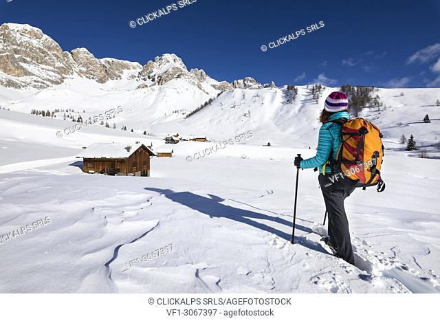 A girl is looking at Fuciace, a small village in Dolomites near San Pellegrino Pass (Soraga di Fassa, Biois Valley, Trento province, Trentino-Alto Adige, Italy