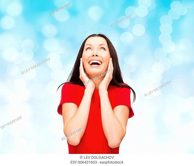 christmas, holidays, valentine's day, celebration and people concept - smiling woman in red dress over blue lights background