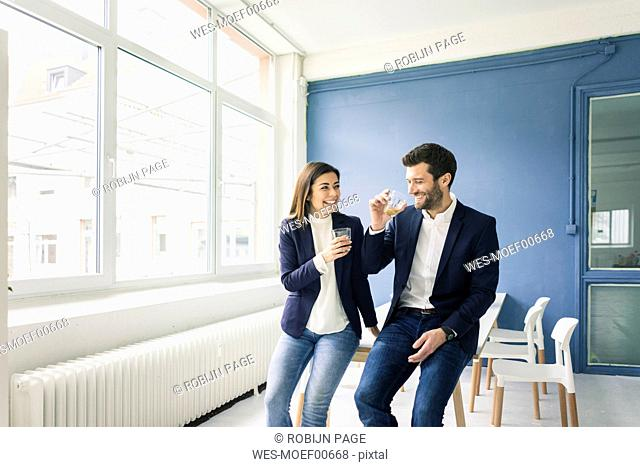 Happy businessman and businesswoman with drinks in office