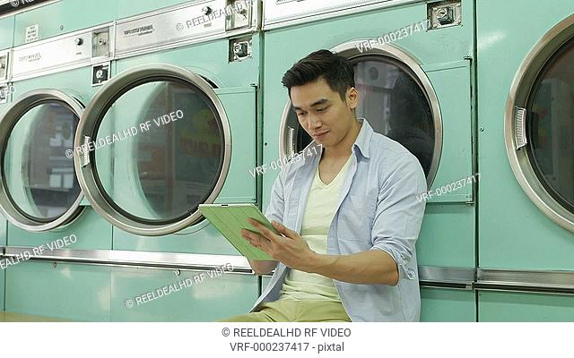 A Young Man sits using his Digital Tablet whilst waiting for his laundry
