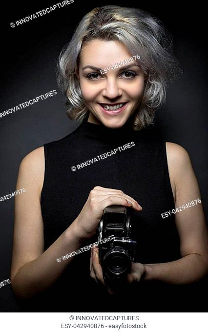Female actor posing with a vintage camera as an artistic director, creative cinematographer or filmmaker. She is advertising the Hollywood movie industry or...