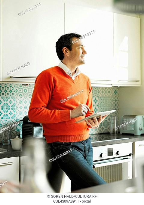 Mature man using tablet in kitchen