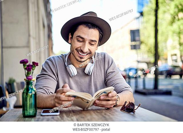 Happy young man reading book at outdoors cafe