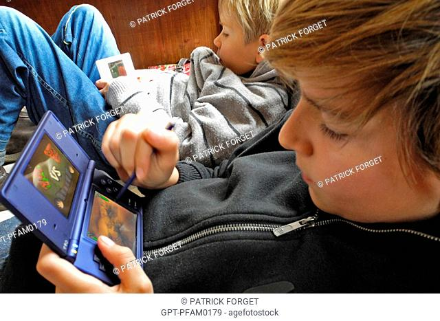 CHILDREN PLAYING VIDEO GAMES NINTENDO DS CONSOLE, EACH TO HIS OWN