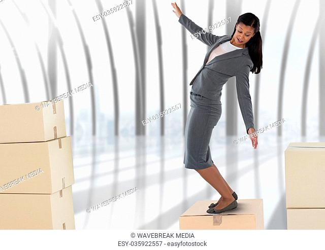 Businesswoman balancing on cardboard boxes by windows
