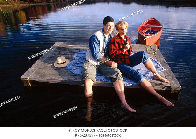 couple relaxing on dock in lake
