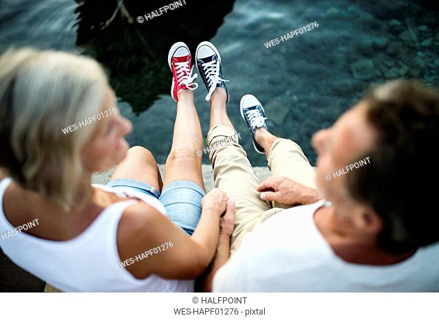 Senior couple sitting on jetty wearing sneakers