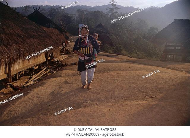 Photograph of a Thai mother and her child on her back walking on the country road
