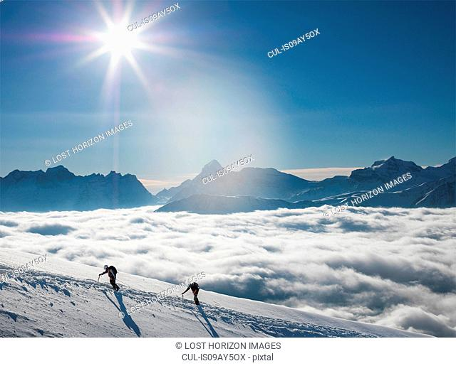 Two climbers on a snowy slope above a sea of fog in an alpine valley, Alps, Canton Wallis, Switzerland