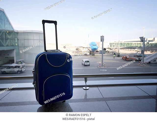 Blue suitcase at airport, airplane in background