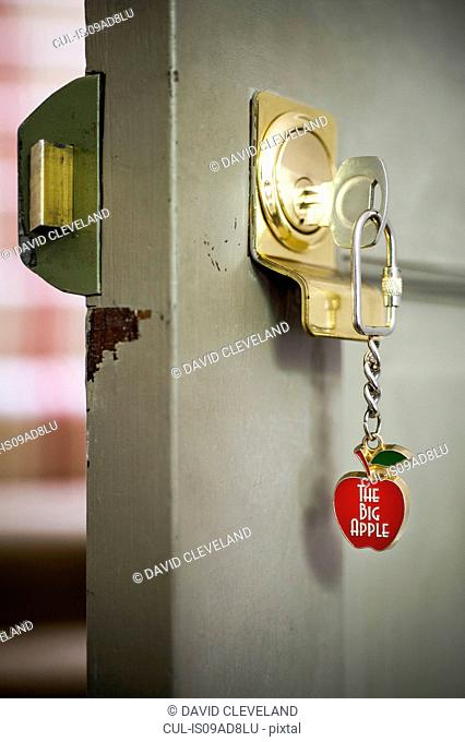 Open front door with key and souvenir keyring