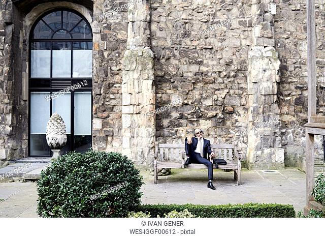 UK, London, senior businessman sitting on bench in a courtyard relaxing while liestening music with headphones