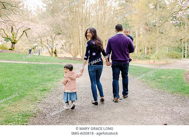 USA, Rear view of family with two children (2-3) in park