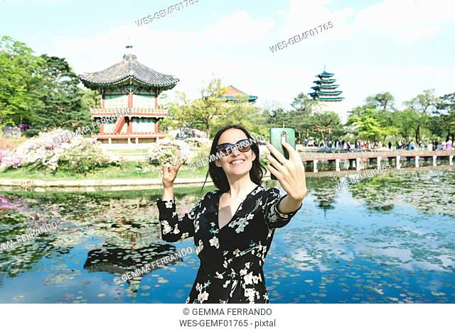 South Korea, Seoul, Woman taking a selfie with smartphone at Gyeongbokgung Palace