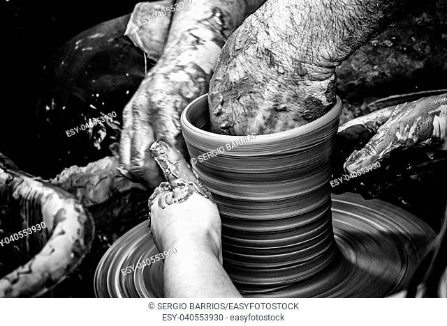 Hands of man working and shaping clay, potter in pottery, craft detail, creation. Spain