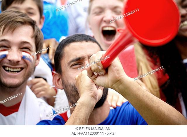 French football supporter playing vuvuzela at match