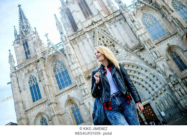 Spain, Barcelona, smiling young woman walking in front of cathedral