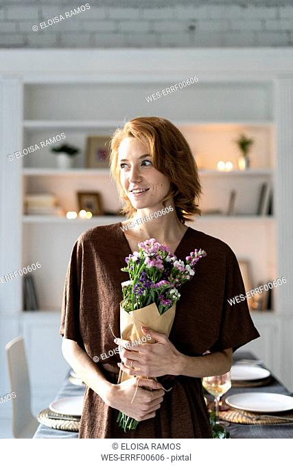 Redheaded woman holding bunch of flowers, standing in front of laid table