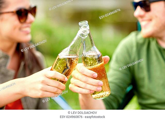 travel, hike, drinks, leisure and people concept - close up of happy couple clinking glass bottles and drinking cider or beer at campsite