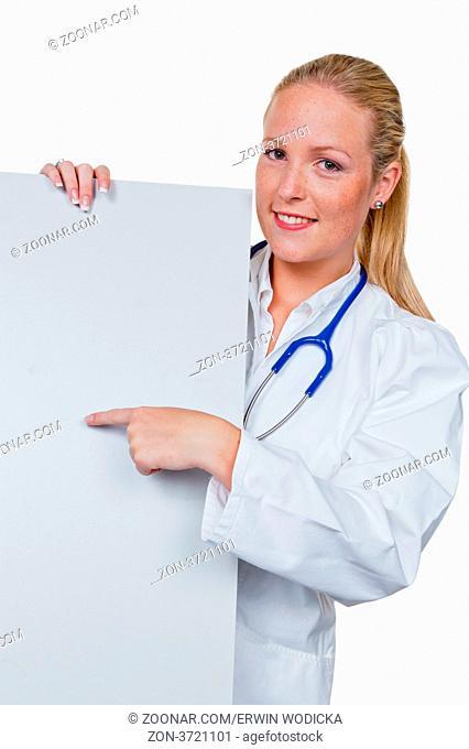 Eine junge Ärztin mit Stethoskop in ihrer Arztpraxis. Hält ein leeres Schild in der Hand