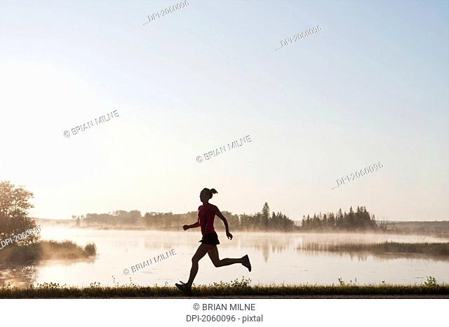 Silohuette Of Woman Running By Lakeshore, Clear Lake, Riding Mountain National Park, Manitoba, Canada