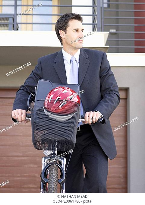 Businessman walking outdoors with bicycle