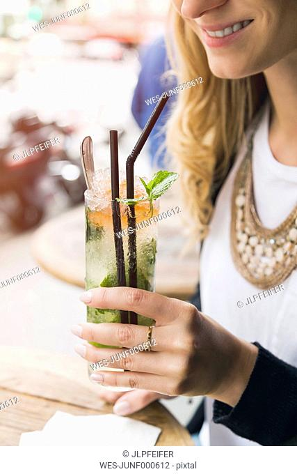 Woman holding glass of Mojito