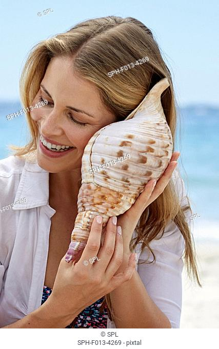 MODEL RELEASED. Woman listening to a seashell