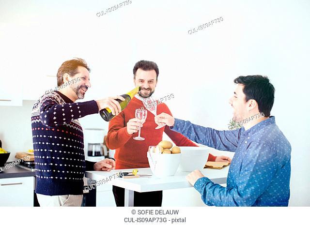Men enjoying champagne while peeling potatoes in kitchen