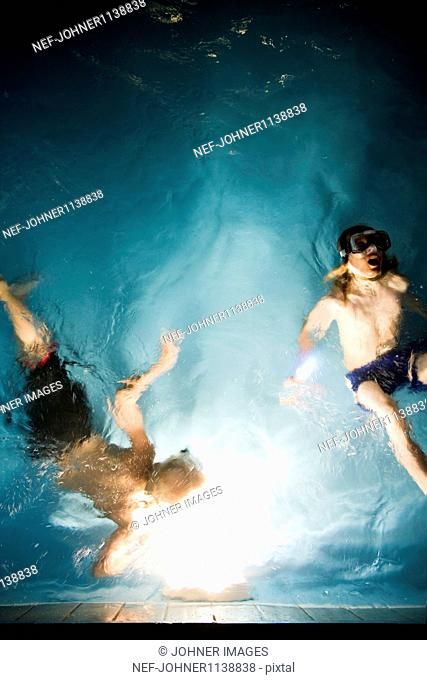 Overhead view of boys swimming in pool at night