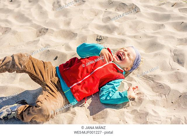Germany, Mecklenburg-Western Pomerania, Ruegen, Schaabe, Boy lying in sand on beach