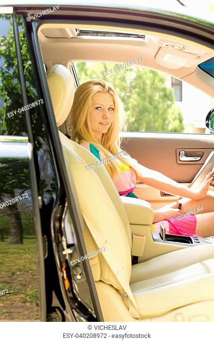 Young attractive blond girl seated in a car with passenger side door open