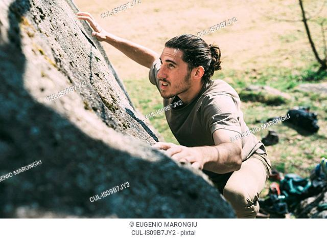 Young male boulderer climbing up boulder, Lombardy, Italy