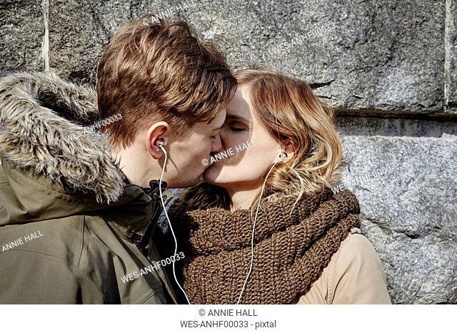 Young couple sharing earbuds kissing at stone wall