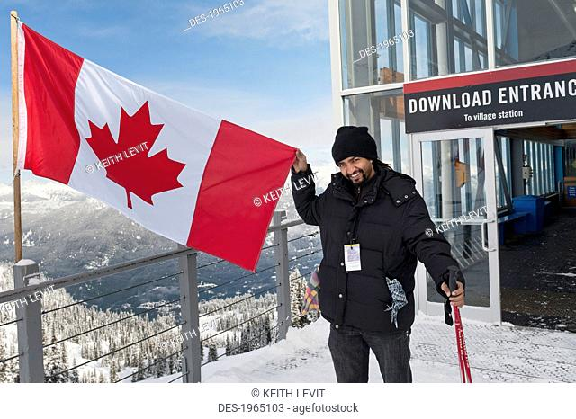 a skiier holds up a canadian flag on a balcony at a ski resort, whistler british columbia canada