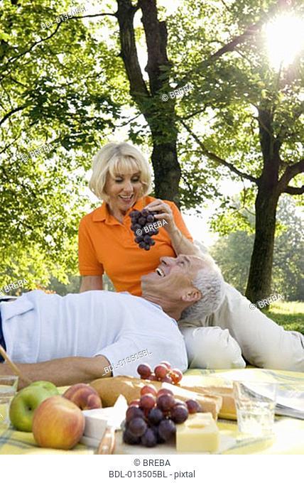 mature woman feeding man grapes at picnic in park