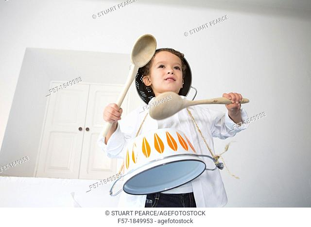 Four year old boy drumming on a saucepan