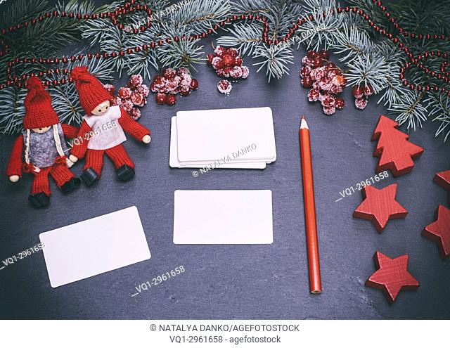 blank white paper business cards on a black background and a red pencil among the Christmas decor