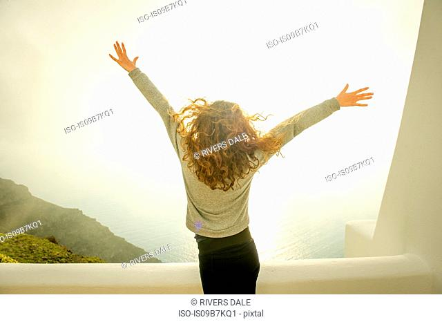 Girl with arms open, sea in background, Oía, Santorini, Kikladhes, Greece