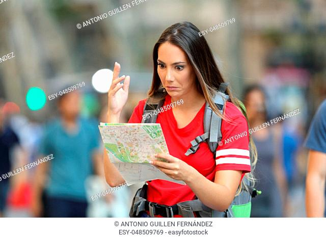 Confused teen tourist searching location in a paper guide walking on the street