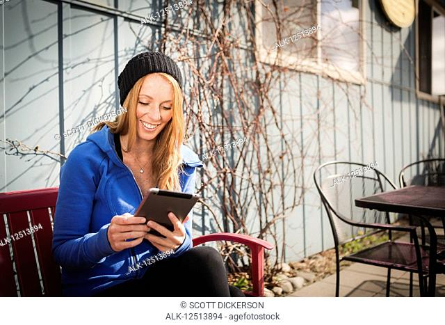 Young woman sitting with her tablet outside a business in downtown Anchorage, South-central Alaska; Anchorage, Alaska, United States of America