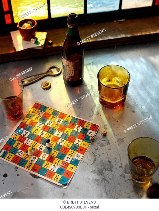 Beer bottle and glasses with board game on pub table