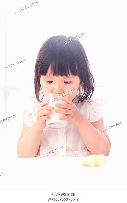 The lovely little girl is having breakfast