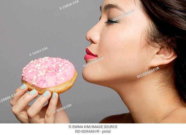 Young woman holding doughnut