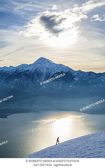 Hiker admires Lake Como and Mount Legnone on a cold winter morning Vercana mountains High Lario Lombardy Italy Europe