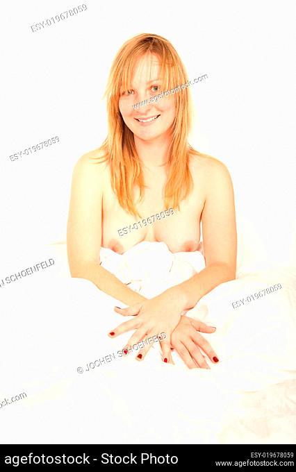 Nackte junge Frau sitzt im Bett