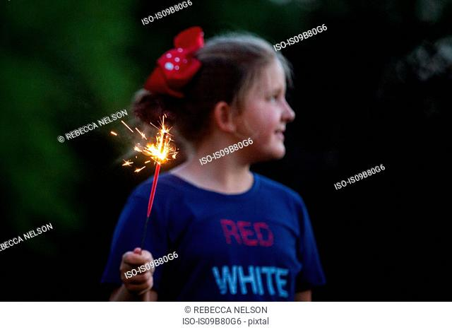 Girl looking away while holding sparkler at night on independence day, USA