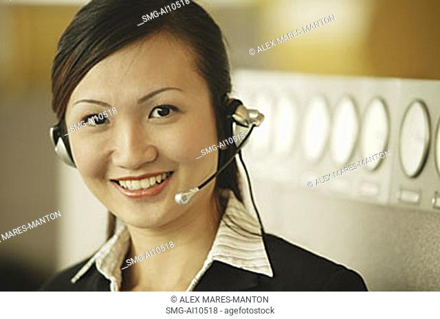 Young woman wearing hands-free device, looking at camera