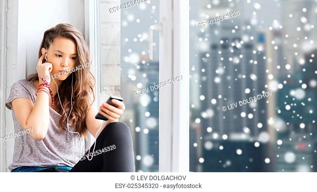 people, technology, winter, christmas and teens concept - sad pretty teenage girl sitting at window with smartphone and earphones listening to music over city...