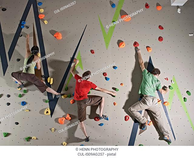 Three adults bouldering on climbing wall